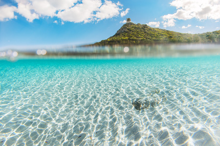 under the surface: Mediterranean coast overlooking the crystal clear sea with white sand and clean - under over sea