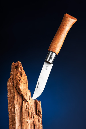 Pocket knife stuck in the wood photo