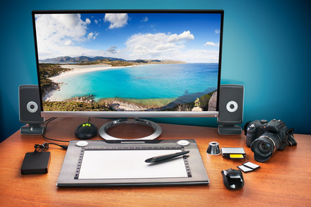 Post production desk with digital camera, memory cards, graphic tablet, and monitor to advertise youself and your work. Monitor with seascape photo. photo