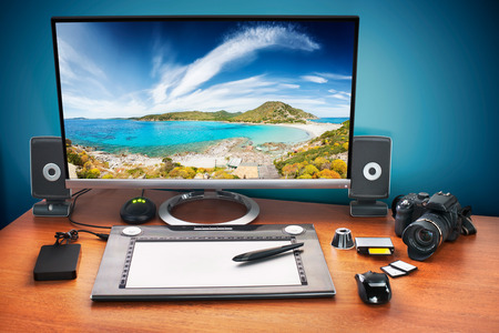 publicidad exterior: Publique escritorio producción con la cámara digital, tarjetas de memoria, tableta gráfica y el monitor a anunciar youself y su trabajo. Monitor con paisaje marino foto.