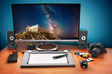 Post production desk with digital camera, memory cards, graphic tablet, and monitor to advertise youself and your work. Monitor with stars photo. photo