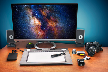 Post production desk with digital camera, memory cards, graphic tablet, and monitor to advertise youself and your work. Monitor with milky way photo. Stockfoto
