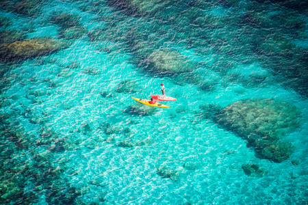 Crystal clear blue sea with two canoeists