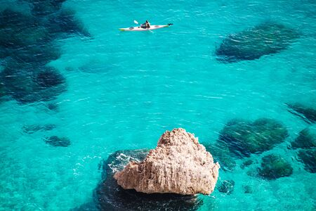 canoeist: Crystal clear blue sea with canoeist and a rock