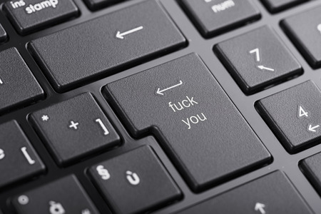 offensive: Computer keyboard with offensive fuck you button, selected focus on enter button