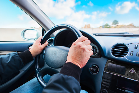 Person driving car with blue sky - example of the position of the hands for safe driving