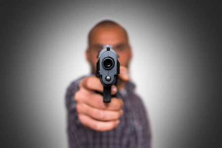 pointed arm: A man aims a semi automatic pistol. Selectively focused on the front of the gun. grey background Stock Photo