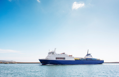Blue and white container ship at the port of Cagliari, in a clear sunny day