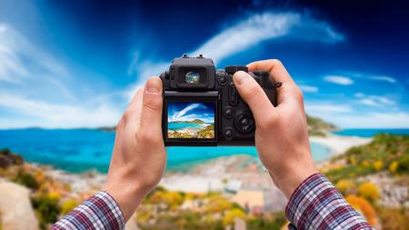 dslr: DSLR camera in hand shooting seascape Stock Photo