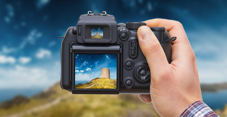 DSLR camera in hand shooting landscape with ancient watchtower -these are photos made by me, that you separately find on my shutterstock portfolio. Logos, brand,has been deleted to be 100% commercial.