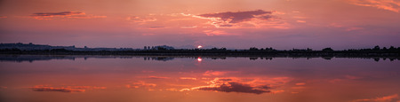 specular: Perfectly specular reflection on the pond at sunset - panoramic Stock Photo