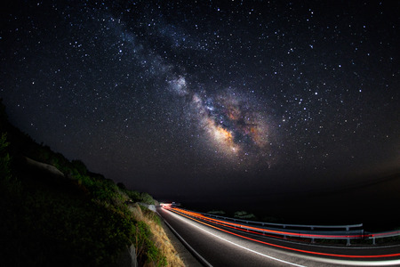 Light trails on the road with the milky way galaxy on the sky (horizontal) - all is in focus because its made with a wide angle lens, and the noise of the sky is very low for this type of pictures. Stock Photo