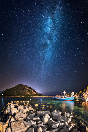 Fisherman boat in a little bay by night under the milky way