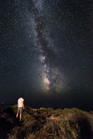family constellation: Lone man looks with amazement at the night sky with the Milky Way - vertical version