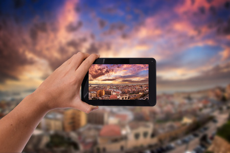 cut out device: Tablet in hand photo shooting sunset landscape