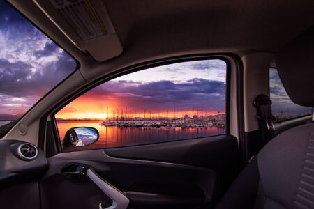 Sunset on marina viewed from inside a car