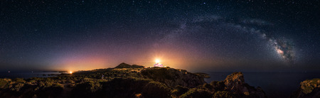360° rectilinear panoramic view of starry night with milky way arc and lighthouse of Capo Spartivento - Very low noise for this type of picture but veri high resolution Stockfoto