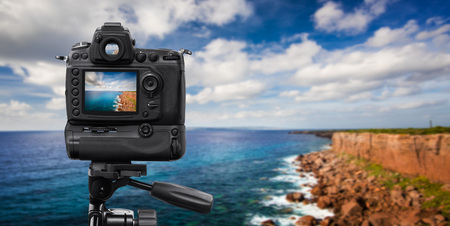 reflex camera: Reflex Camera on tripod over a cliff, performing a long exposure Stock Photo