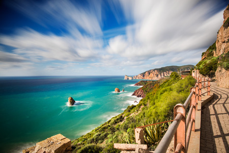 rough sea: Walkway along the Mediterranean coast with rough sea and blue sky in long exposure