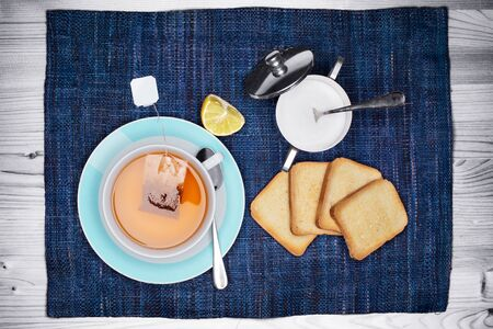 dietetic: Overhead view of a cup of tea with rusks and sugar bowl on blue placemat over a white wooden table. Typical healthy and dietetic breakfast.