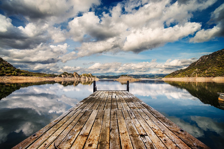 in perspective: Perspective view of a wooden pier in a completely calm lake with reflections of the sky