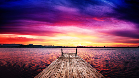 Perspective view of a wooden pier in a fiery sunset over the bay