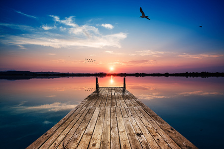 Perspective view of a wooden pier on the pond at sunset with perfectly specular reflection Banco de Imagens