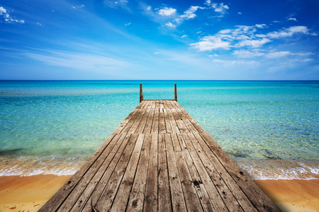 Perspective view of a wooden pier on the seashore with clear blue sea Stockfoto