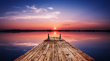 Vue en perspective d'une jetée en bois sur l'étang au coucher du soleil avec la réflexion spéculaire parfaitement