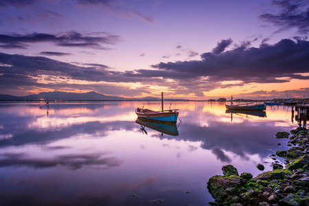 specular: Perfect calm lagoon creates amazing reflection at sunset with a boat in the center - specular natural image Stock Photo