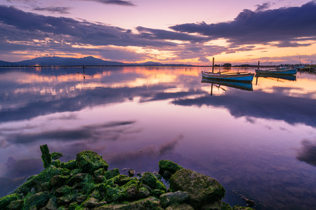 sky reflection: Perfect calm lagoon creates amazing reflection at sunset with a fisherman boat - specular natural image
