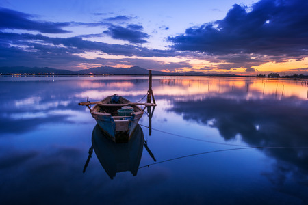 specular: Perfect calm lagoon creates amazing reflection after the sunset with a fisherman boat - specular natural image at the blue hour