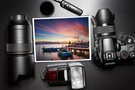 deleted: Camera equipment around a printed photo of a sunset at the lagoon - In this photo the logos, brand, or anything that can bring to a particular object has been deleted to be 100% commercial.