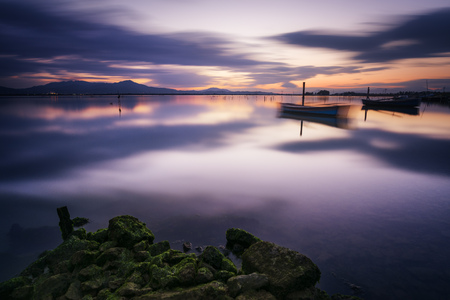 sky reflection: Perfect calm lagoon creates amazing reflection at sunset with a fisherman boat - long exposure Stock Photo