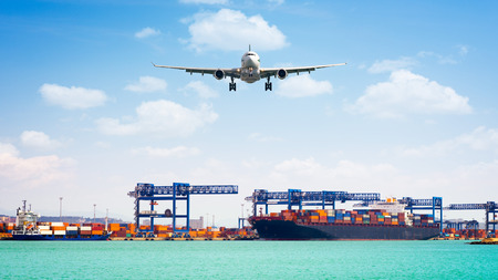 Container cargo freight ship with working crane loading bridge in shipyard, and cargo plane in front of the harbor, for logistic Import export background Stock Photo