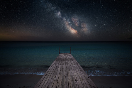 Milky way over che seashore and small wooden jetty in perspective
