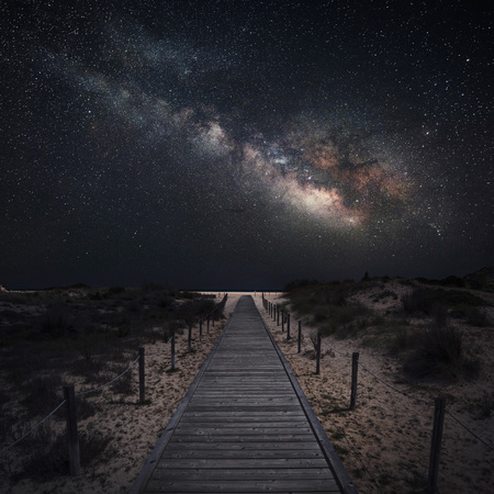 Milky way over a wooden walkway in perspective near a beach