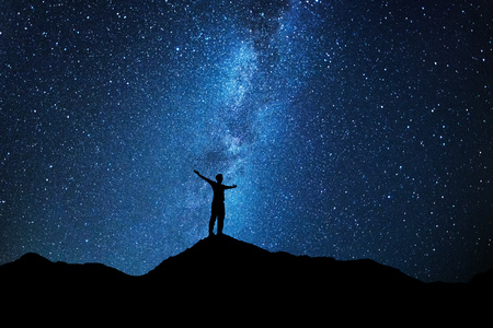 Man who feels on top of the world looking at the milky way