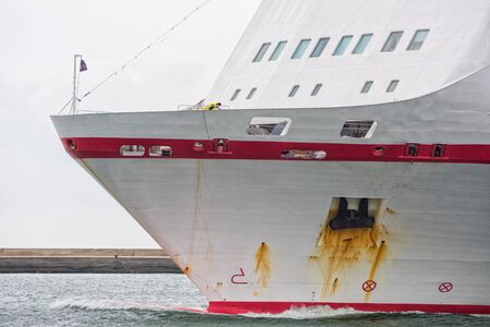 enters: The prow of a passenger ship that enters the port