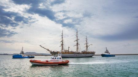 escorted: Cagliari, Italy: 30042016; Italian Navy Ship, Amerigo Vespucci is entering the port of Cagliari escorted by two tugboats and a patrol boat of the Coast Guard Editorial