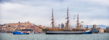 escorted: Cagliari, Italy: 30042016; Italian Navy Ship, Amerigo Vespucci performs maneuver mooring escorted by tugs, and in the background the city of Cagliari