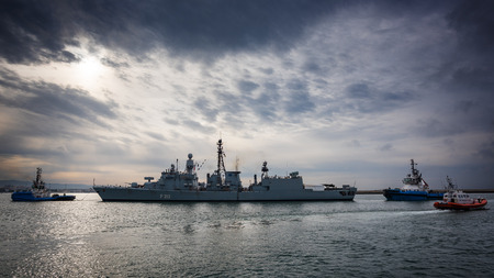 escorted: Cagliari, Italy: 30042016; German military ship enters the port escorted by two tugboats