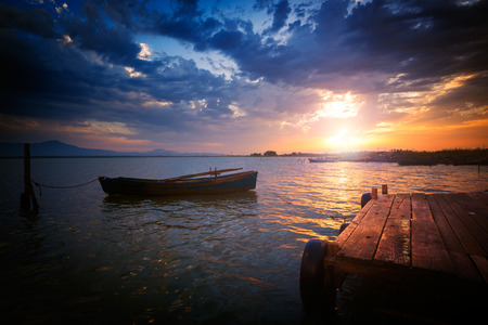 irish countryside: Colorful sunset over the pond with a wooden jetty and a boat