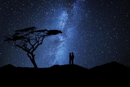 Paar liefhebbers silhouet kussen in de buurt van een boom onder een hemel vol sterren