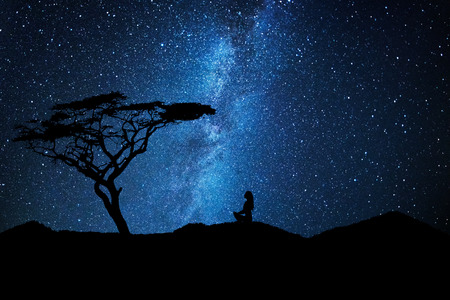 Woman silhouette near a tree meditates under a sky full of stars galaxy Standard-Bild