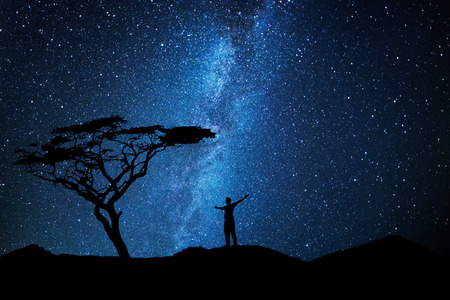 Man silhouette admiring the sky full of stars near a tree