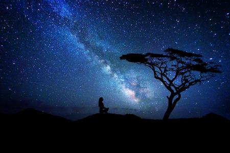Woman silhouette near a tree meditates under the milky way galaxy