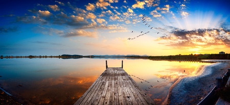 sunrise ocean: Perspective view of a wooden pier on the pond at sunset with perfectly specular reflection Stock Photo