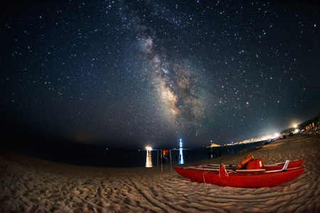 Red rescue boat on the beach under the milky way galaxy