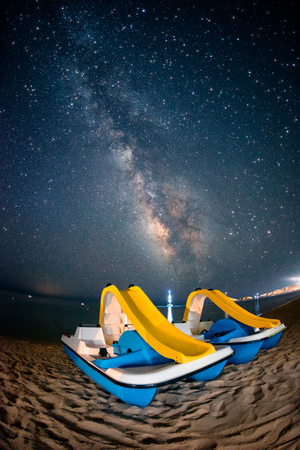 Colorful pedalos on the beach under the milky way galaxy